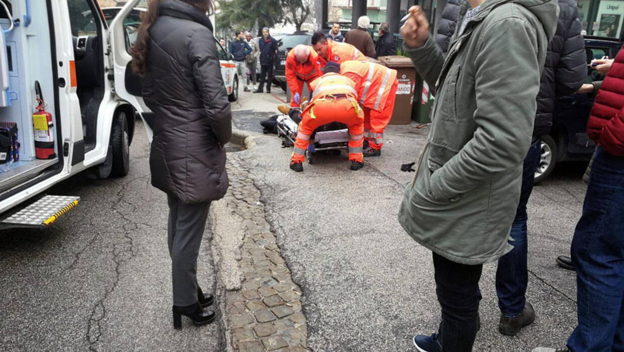 epa06493400 Paramedics treat an injured person that was shot from a passing vehicle in Macerata, Italy, 03 February 2018. According to the local authorities, the town at the eastern Italian coast near Ancona is under a lockdown due to shots being fired from a car that is driving around in the town for yet unknown reasons.  EPA/GUIDO PICCHIO  Dostawca: PAP/EPA. PAP/EPA © 2018 / GUIDO PICCHIO