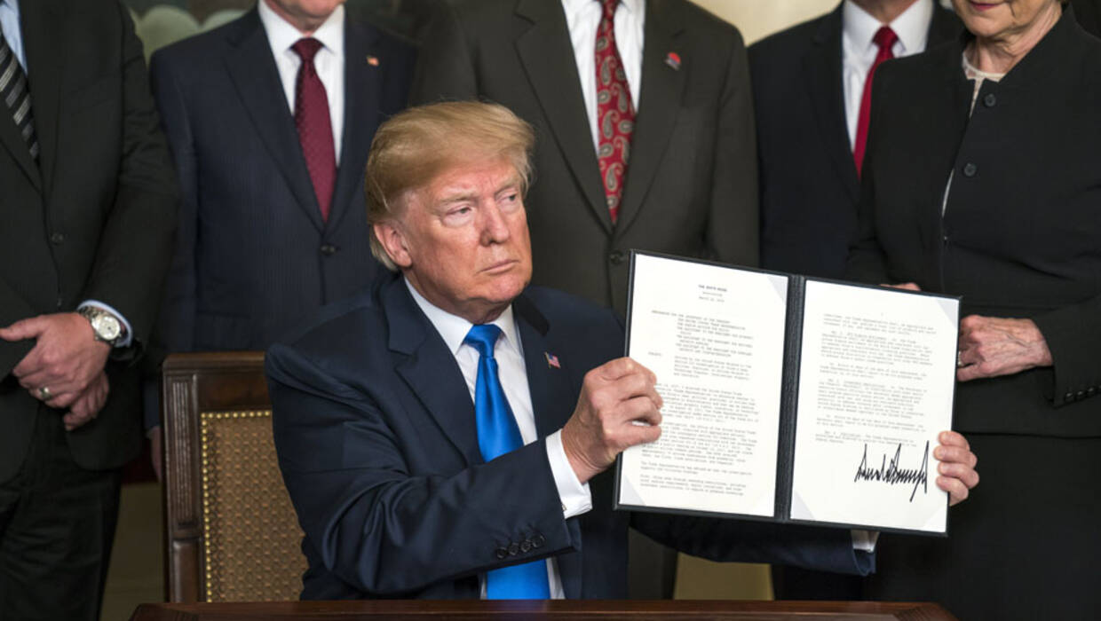 US President Donald J. Trump (C) raises a presidential memorandum targeting what the White House termed 'China's economic aggression' in the Roosevelt Room of the White House in Washington, DC, USA, 22 March 2018. China is threatening retaliation for the tariffs on $50 billion US dollars (40 billion euros) of Chinese imports, sparking further fears of a trade war. Fot. PAP/EPA/JIM LO SCALZO