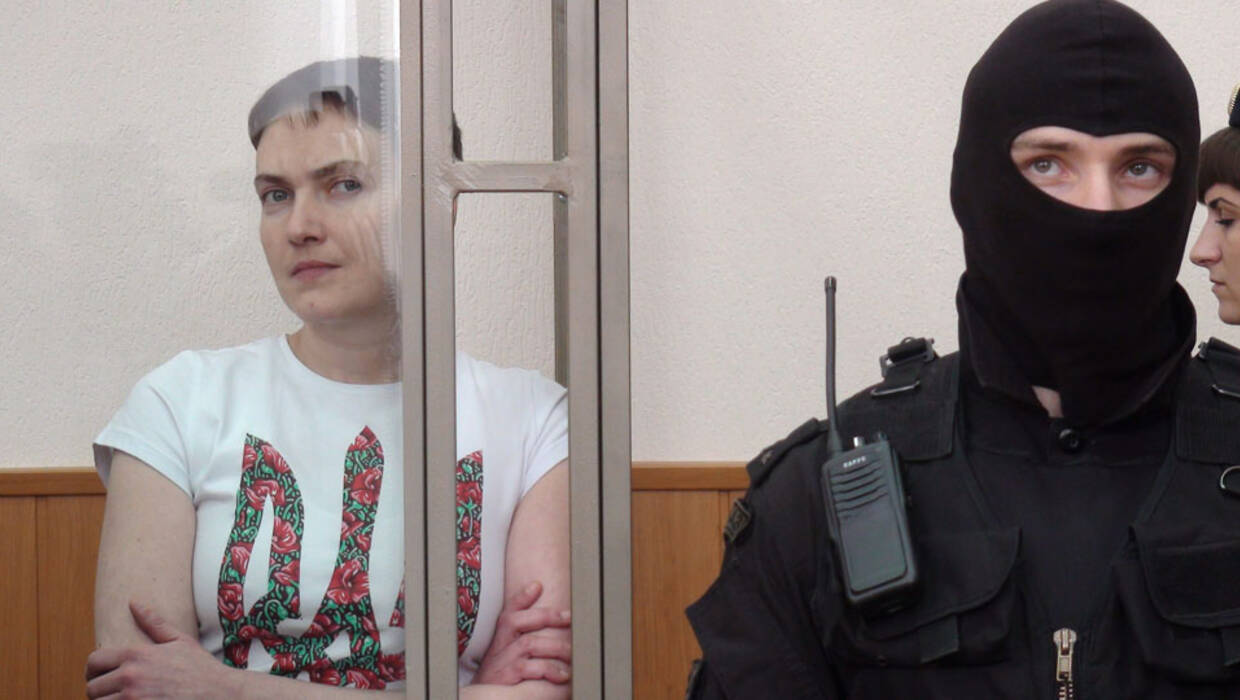 epa05223948 Former Ukrainian military pilot Nadezhda Savchenko (L) inside a glass cage during a court hearing at the Donetsk district court in Donetsk, Rostov Region, Russia, 21 March 2016. The court found Nadezhda Savchenko guilty in assistance of killing Russian TV journalists and started reading the verdict. EPA/STRINGER Dostawca: PAP/EPA. PAP/EPA © 2016 / STRINGER